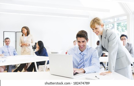 Female Supervisor Assisting Employee at Laptop