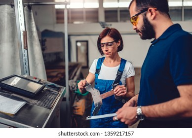 Female supervisor measuring cut out product on CNC machine and talking with operator