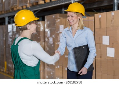 Female supervisor and storage worker shaking hands