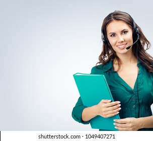 Female support phone operator in headset, green confident clothing with folder, empty copyspace area for slogan or advertising text message, over grey. Call center and customer support service concept
