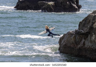 Female surfer diving into the water