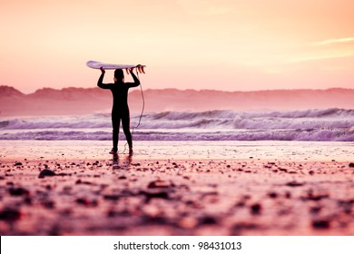 Female surfer on the beach at the sunset