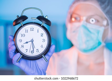 Female surgeon medical specialist with clock emphasizing the importance of regular health care medical exams