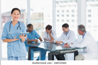 Female surgeon using digital tablet with group around table in background at hospital