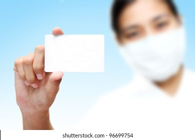 female in surgical mask holding blank card