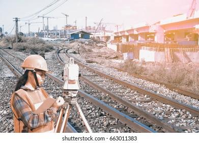 Female Surveyor or Engineer making measure by Theodolite on the railway tracks.