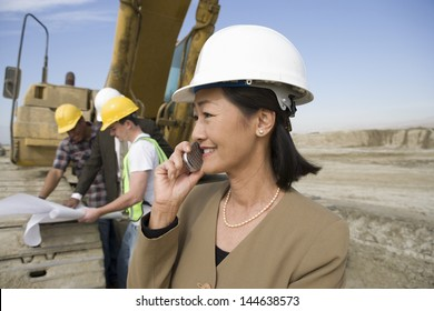 Female surveyor in hard hat in front of workers and heavy machinery using cellphone on site
