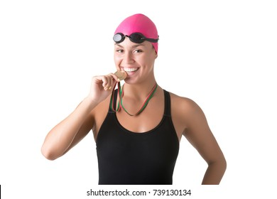 Female swimmer biting her medal after winning, isolated in white