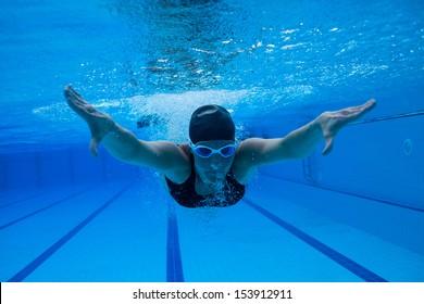 Female swimmer diving underwater in swimming pool