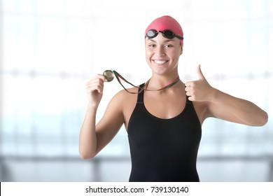 Female swimmer holding her medal after winning