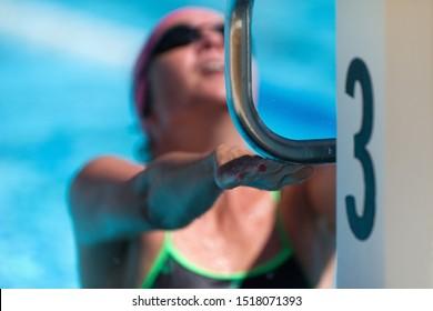Female swimmer holding onto starting block preparing to swim backstroke