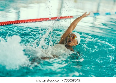 Female swimmer on training in the swimming pool. Backstroke swimming style