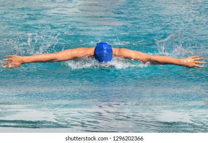 Female swimmer is swimming in butterfly stroke during competition in to the pool