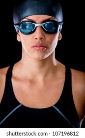 Female swimmer wearing goggles and hat - isolated over a black background