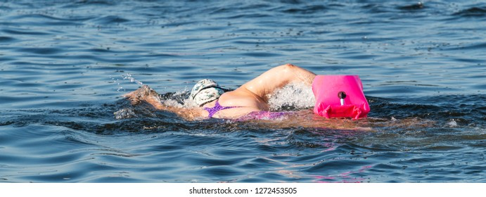 A female is swimming in the Long Island Sound with a pink flotation device strapped to her waist