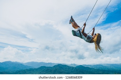 Female swinging over a mountain view in the clouds