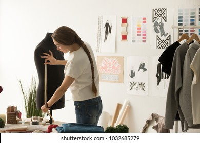 Female tailor or seamstress taking mannequin measurements for cloth pattern with measuring tape in fashion design studio, woman designer working with dummy in workshop, dressmaking and sewing concept