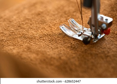 Female tailor threading leather material on sewing machine