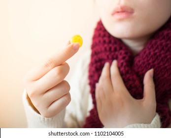 Female taking medical lozenges with honey lemon flavored for relief sore throat, irritating cough and mouth pain. Close up of girl with scarf feeling sick and cold in winter. Health care concept.