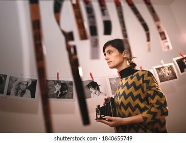 Female taking photo with old camera. Portrait of creative girl photographer in photo studio darkroom. Developing analog camera film