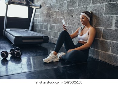 Female taking a rest after workout and using cellphone