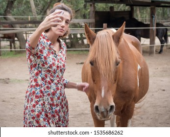 Female taking a selfie with a piebald horse.