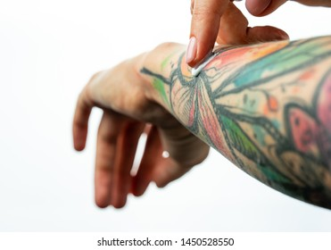 Female tattooed hands hold a jar of cream. Fingers apply cream to skin. Close up