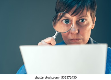 Female tax inspector looking at corporate financial documents with magnifying glass