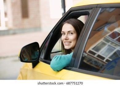 Female taxi driver sitting in yellow car