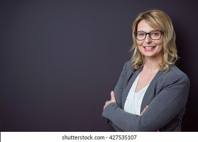 Female teacher with blond hair and glasses stands near black background with arms crossed and smiling