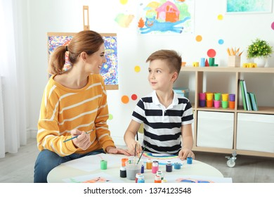 Female teacher with child at painting lesson indoors
