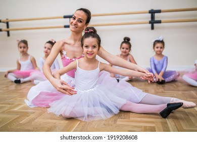 Female teacher exercising with a group of little girls dancing ballet in the class.