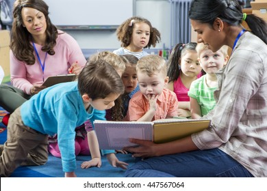 Female teacher giving a lesson to nursery students. They are sitting on the floor and there is a teacher taking notes.