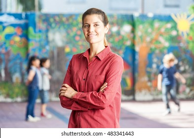 Female teacher happy with her classroom playing in courtyard.