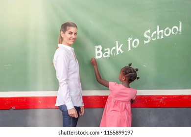 Female teacher happy in primary classroom with african pupil writing back to school sign on the chalkboard.