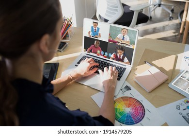 Female teacher having a video conference with multiple students on laptop at school. distance learning online education concept