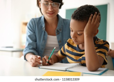 Female teacher helping child with assignment at school