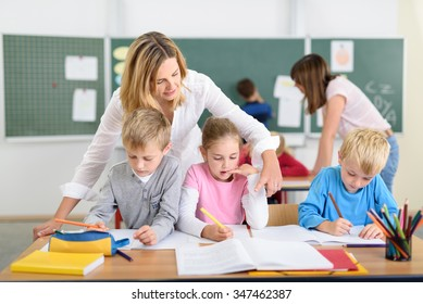 Female Teacher Helping her Young Students Answering Exam Inside the Classroom.