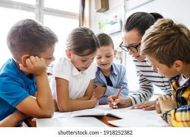Female teacher helps school kids to finish they lesson.They sitting all together at one desk.