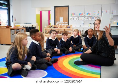 Female teacher holding up a book in front of her class of elementary school kids sitting on the floor in a classroom, side view