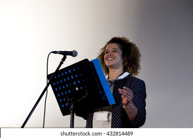 Female teacher making a speech in a lecture hall. She is standing at the podium and smiling to the crowd.