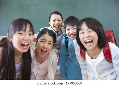 Female teacher and Primary Japanese boy and Japanese girl with a smile