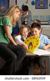 Female Teacher In Primary School Teaching Children To Tell Time In Classroom