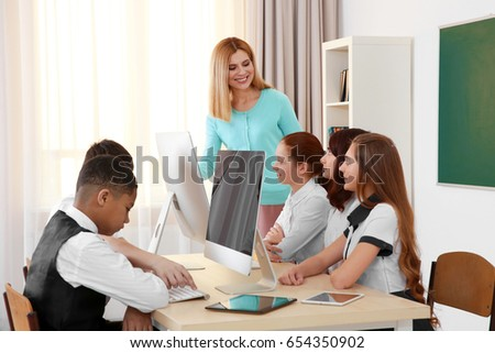 female teacher pupils working computers classroom stock photo edit