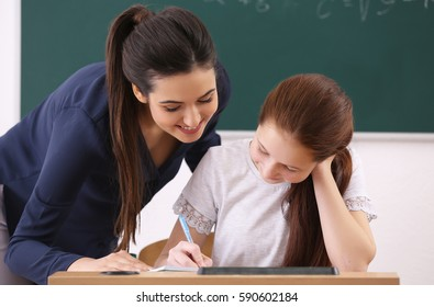 Female teacher and schoolboy doing task in classroom