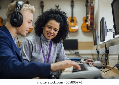 Female teacher is sitting with one of her students in a music lesson at school. He is learning to play the keyboard and is wearing headphones.
