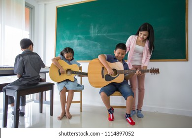 Female Teacher Teaching Guitar With Boy Student In Classroom
