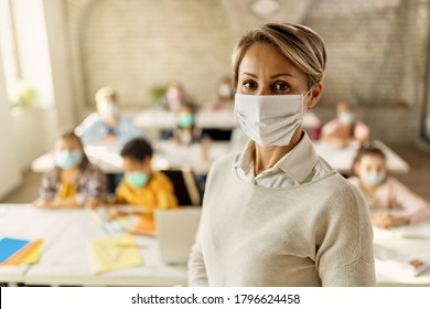 Female teacher wearing a face mask while teaching children at elementary school and looking at camera.