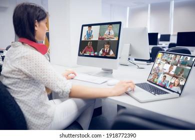 Profesora que usa auriculares con videollamada con múltiples estudiantes en la escuela en laptop y computadora. concepto de educación en línea a distancia