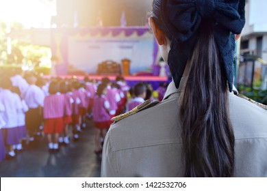 Female teachers wear Thai government uniforms behind the scenes as primary students are lining up.